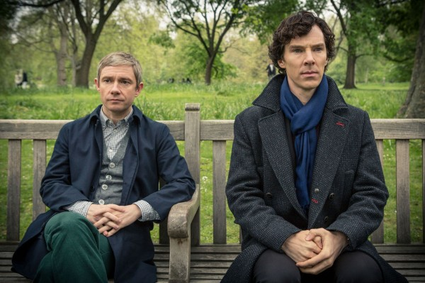 Martin Freeman as John Watson and Benedict Cumberbatch as Sherlock Holmes sitting on a bench