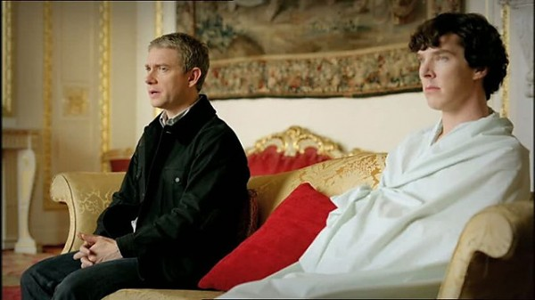 Benedict Cumberbatch as Sherlock Holmes wrapped in a sheet sitting on a sofa with Martin Freeman as John Watson