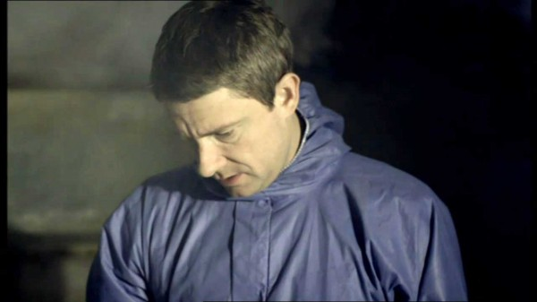 Martin Freeman as John Watson on the BBC series Sherlock in a crime scene jumpsuit looking down
