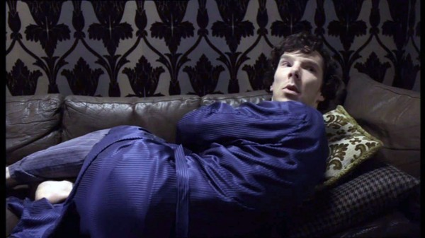 Benedict Cumberbatch as BBC Sherlock curled up on sofa looking up to ask a question