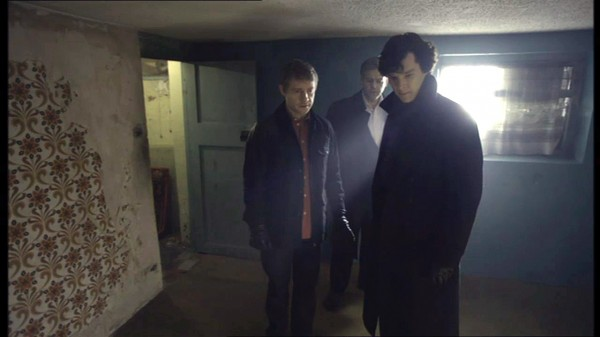 Martin Freeman as John Watson, Benedict Cumberbatch as Sherlock Holmes, Rupert Graves as Lestrade look at something on the floor in a disused and abused apartment