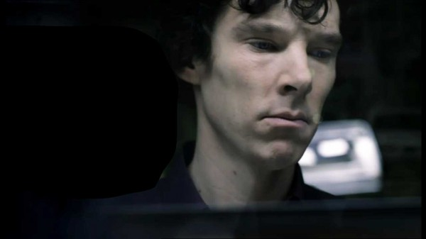 Benedict Cumberbatch as Sherlock Holmes in the BBC series Sherlock looking sad and pouty through a rain washed window