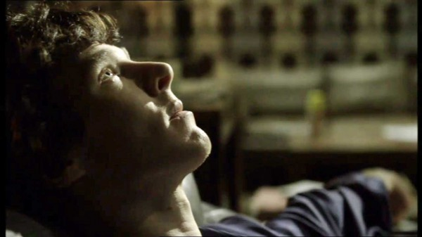 Benedict Cumberbatch as Sherlock Holmes lying on the sofa staring at the ceiling