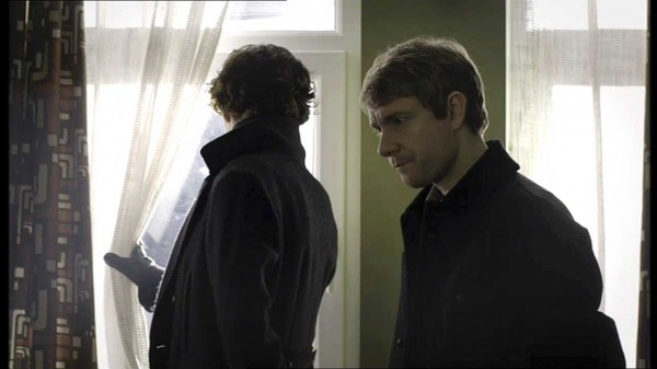 Benedict Cumberbatch as Sherlock Holmes looking out a window while Martin Freeman as Dr. John Watson looks pensive