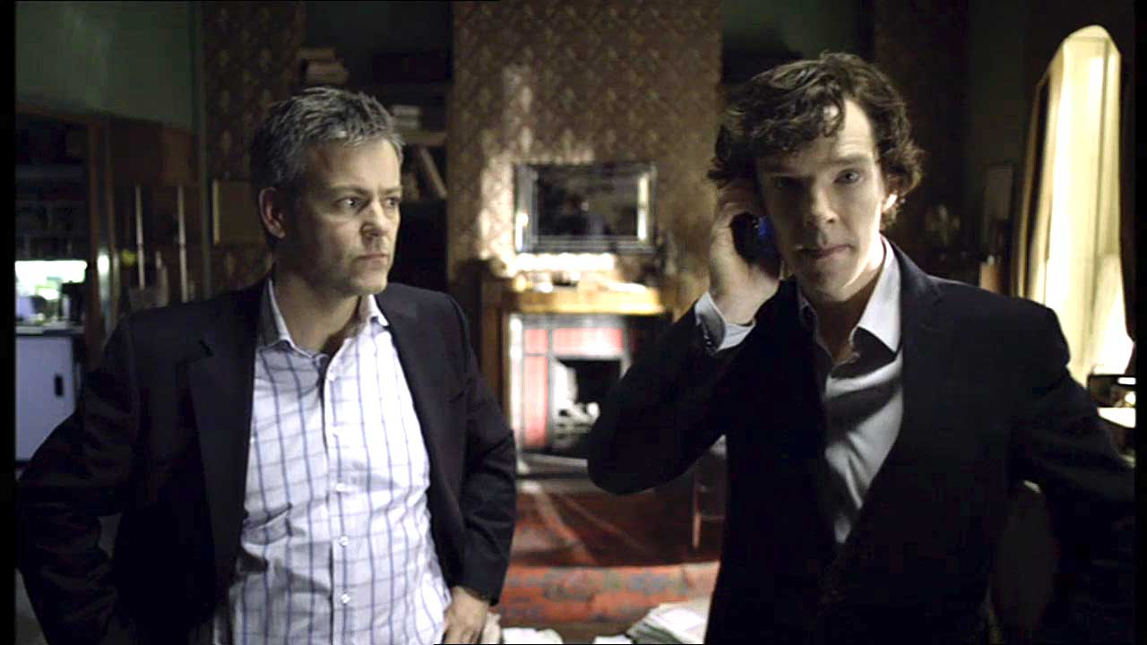 Rupert Graves as Greg Lestrade is looking skeptically at an enthusiastic Benedict Cumberbatch as Sherlock
