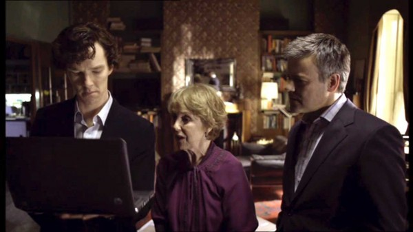 Benedict Cumberbatch as Sherlock Holmes in the BBC series Sherlock looking intently at a computer screen with Mrs. Hudson and Inspector Lestrade