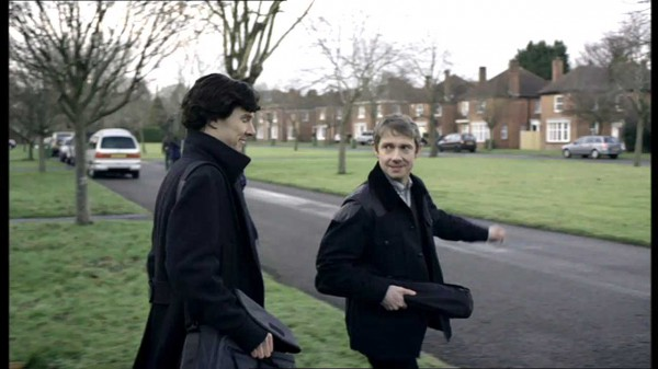 Benedict Cumberbatch as Sherlock Holmes and Martin Freeman as John Watson in BBC series Sherlock walking in a green area smiling and holding large bags