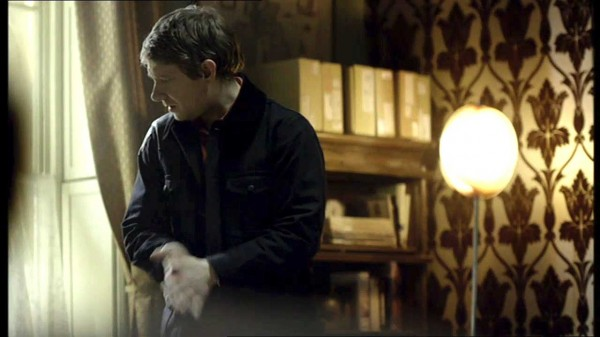 Martin Freeman as John Watson in the BBC series Sherlock rubbing his hands together as he looks out a window