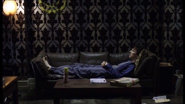 Benedict Cumberbatch as BBC Sherlock Holmes lying on sofa in dressing gown and pajamas