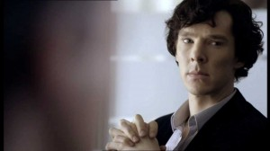Benedict Cumberbatch as Sherlock Holmes looking serious with hands clasped.