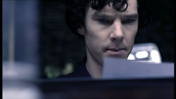 Benedict Cumberbatch as BBC Sherlock Holmes looking disapprovingly at a paper he's reading