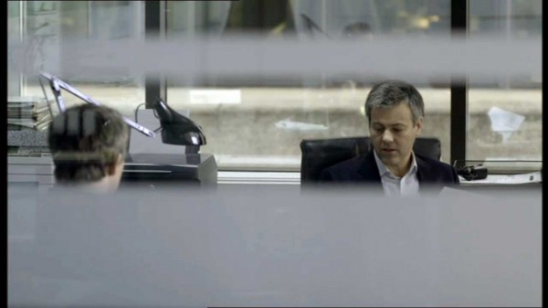 Rupert GRaves as Detective Inspector Lestrade in BBC series Sherlock looking down at his desk as we watch through blinds