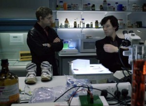 Martin Freeman as John Watson and Benedict Cumberbatch as Holmes in BBC Sherlock discussing evidence in the lab