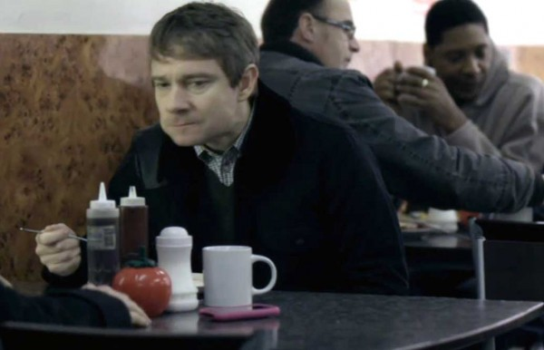 Martin Freeman as Dr. John Watson eating with a suspicious look on his face