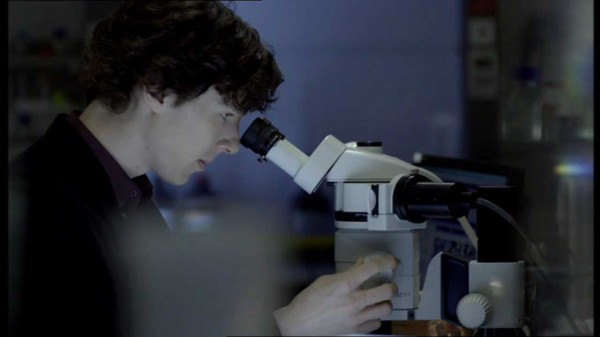 Benedict Cumberbatch as Sherlock Holmes in BBC Sherlock peering through a microscope in profile