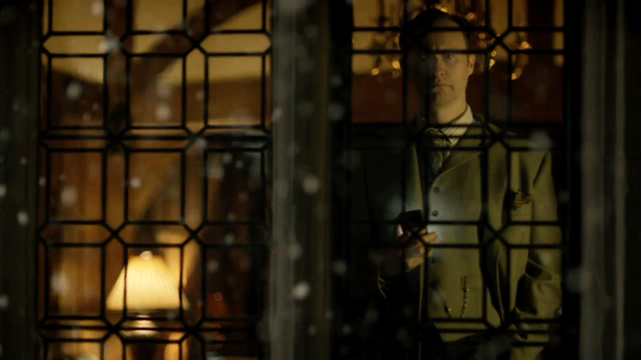 Mark Gatiss as BBC Sherlock Mycroft Holmes standing front of a mullioned window with a mobile cell phone