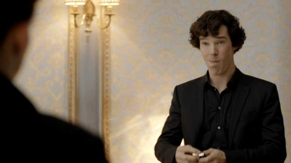 Benedict Cumberbatch as Sherlock Holmes in the BBC series Sherlock standing, looking as if he has a huge wad of something stuck in his right jaw