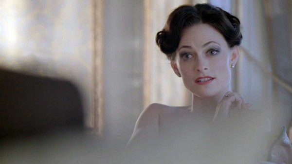 Lara Pulver as Irene Adler in the BBC series Sherlock seated naked with a questioning expression