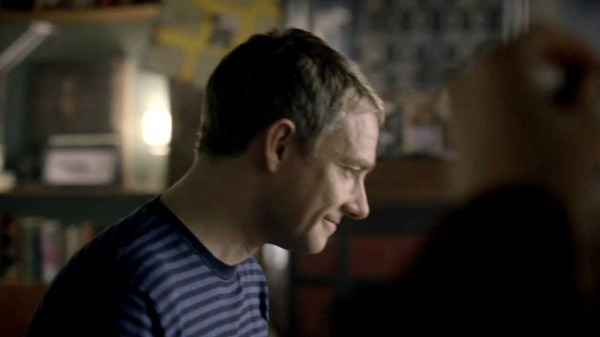 Martin Freeman as Dr. John Watson in BBC series Sherlock smirking as he peers at something table height