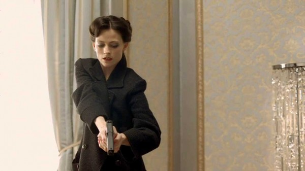 Lara Pulver as Irene Adler in the BBC series Sherlock pointing a gun at someone on the floor