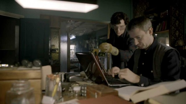 Benedict Cumberbatch as Sherlock Holmes and Martin Freeman as John Watson in the BBC series Sherlock looking at a computer screen with Sherlock wearing goggles and holding a blow torch