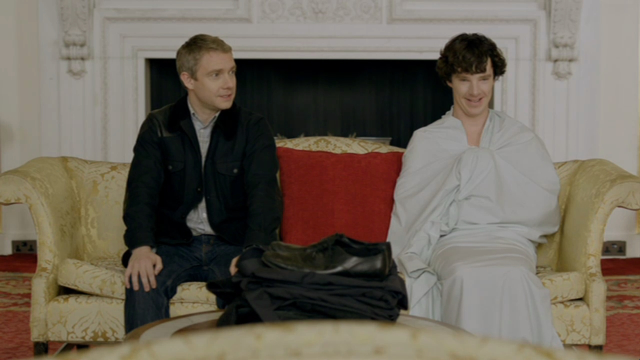 Martin Freeman as John Watson looking at Benedict Cumberbatch as BBC Sherlock Holmes wrapped in just a sheet
