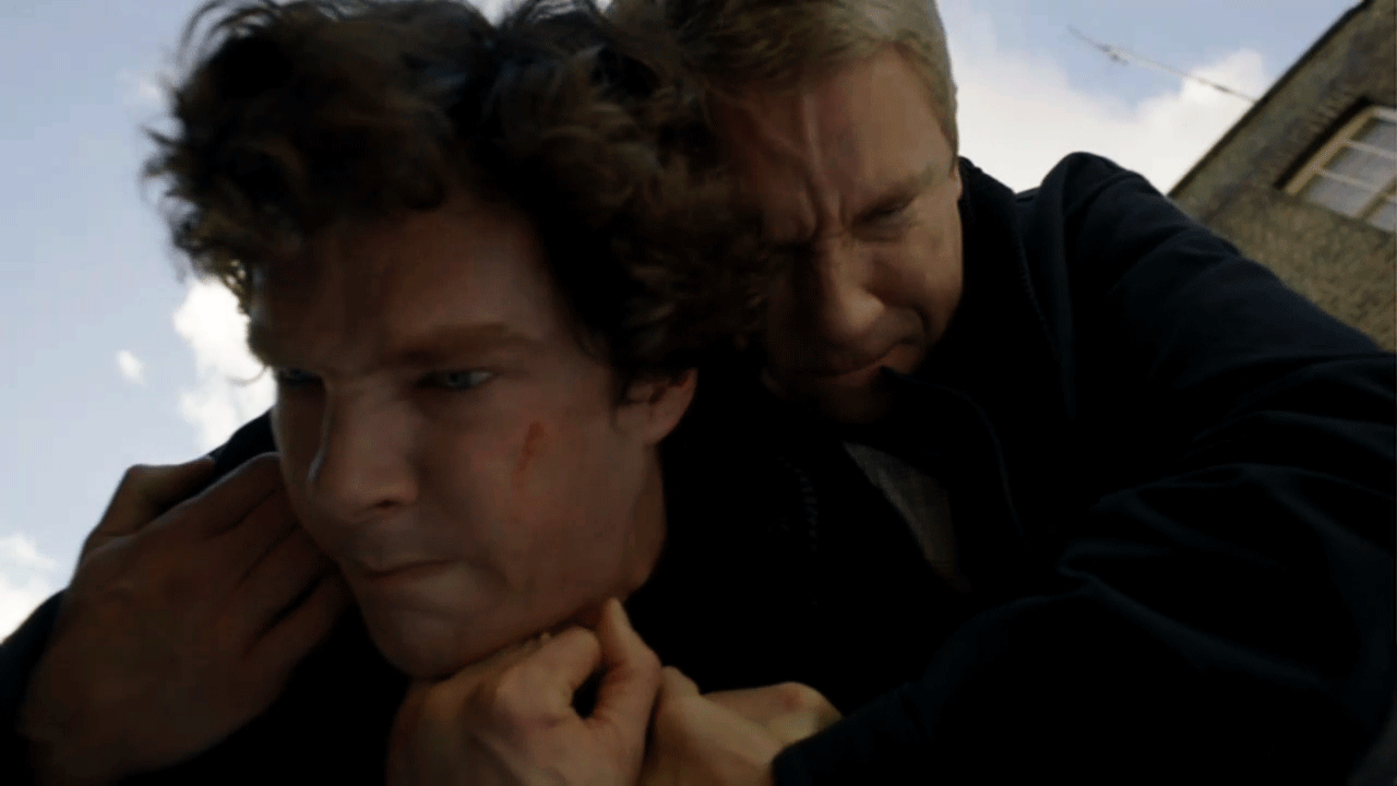 Benedict Cumberbatch as Sherlock Holmes fighting and grappling with Martin Freeman as John Watson