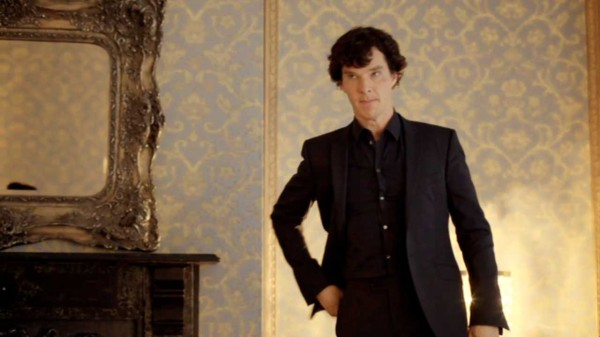 Benedict Cumberbatch as Sherlock Holmes in the BBC series Sherlock standing looking angry as he puts his hand in his pocket