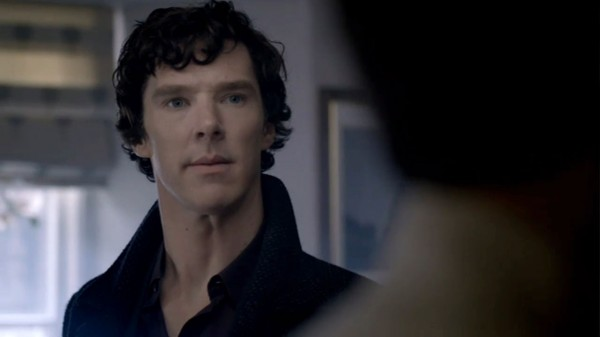 Benedict Cumberbatch as BBC Sherlock Holmes listening intently with a skeptical look on his face