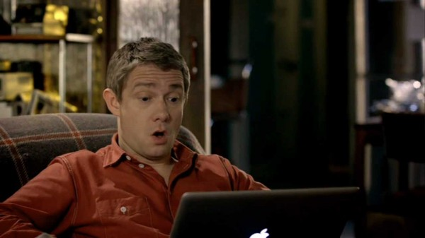 "Martin FReeman as John Watson in BBC Sherlock staring at a laptop screen with his mouth open in an ""oh!"""