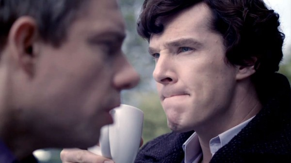 Martin Freeman as John Watson in the foreground and Benedict Cumberbatch as BBC Sherlock lips pinched pondering in background