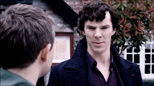 Benedict Cumberbatch as Sherlock Holmes in the BBC series Sherlock scowling with a double banned of wrinkles at the bridge of his nose