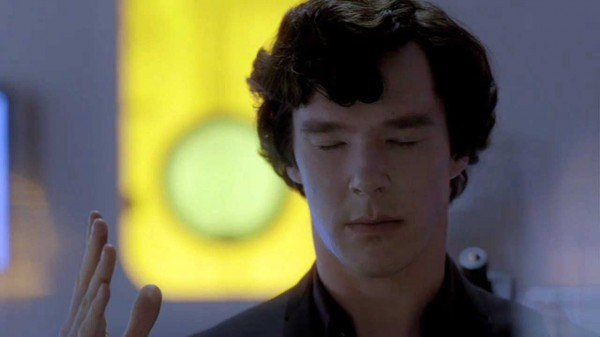Benedict Cumberbatch as Sherlock Holmes in the BBC series Sherlock sitting with his eyes closed and hand up as if in meditation