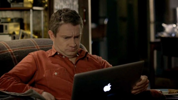 Martin Freeman as John Watson in BBC Sherlock looking puzzled at a laptop screen