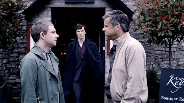 martin Freeman as John Watson in the BBC Series Sherlock is looking at Rupert Graves as Greg Lestrade who is puffing out his cheeks as a disgruntled looking Benedict Cumberbatch as Sherlock Holmes approaches