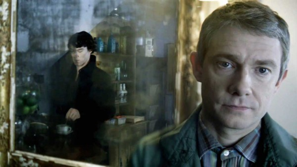Benedict Cumberbatch as Sherlock Holmes seen in a mirror stirring coffee intended for Martin Freeman in the foreground as John Watson in BBC Sherlock