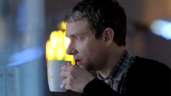Martin Freeman as John Watson in the BBC series Sherlock about to take a sip from a coffee mug looking questioningly at someone off camera