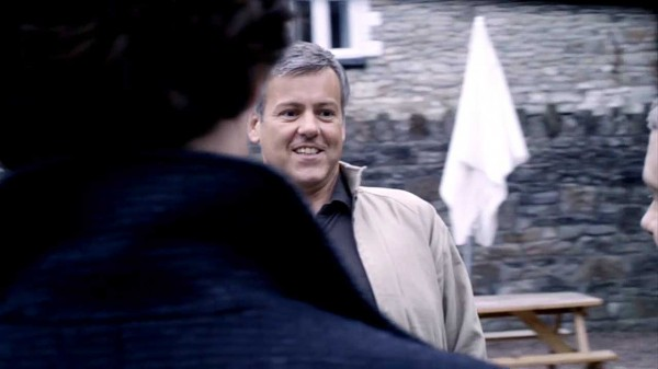 Rupert Graves as Detective Inspector Greg Lestrade in the BBC sereis Sherlock smiling a bit nervously at Sherlock Holmes and John Watson