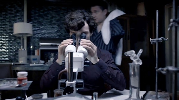 Martin Freeman as John Watson in BBC Sherlock walks behind Benedict Cumberbatch as Sherlock Holmes peering in a microscope