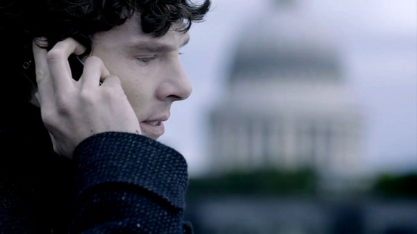 Benedict Cumberbatch as Sherlock Holmes in the BBC series Sherlock on a roof with a mobile phone against his ear and the top of St. Paul's Cathedral behind him