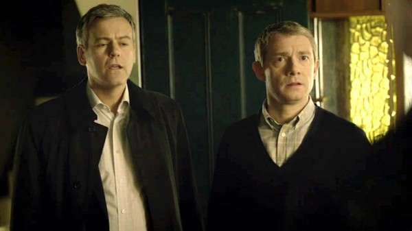 Rupert Graves as D.I. Lestrade in the BBC series Sherlock looks below the waist as Martin Freeman as Dr. John Watson looks at Sherlock Holmes face with a startled expression.