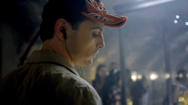 Andrew Scott as James Moriarty from the BBC series Sherlock in British flag ball cap and with ear buds in his ears looking down with a serious expression at his iPod