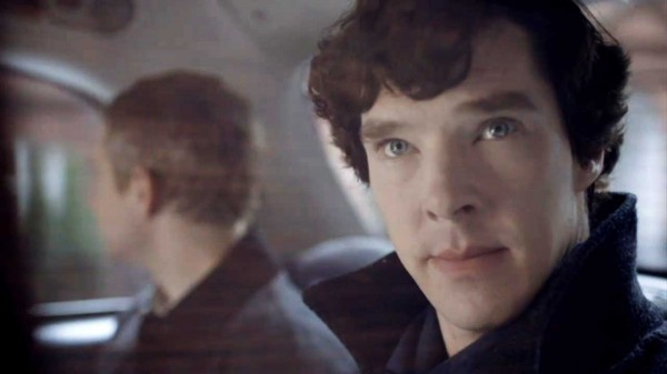 Benedict Cumberbatch as Sherlock Holmes in the BBC series Sherlock looking out the window of taxi cab alertly sitting besides Martin Freeman as John Watson