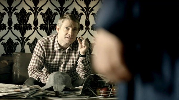 Martin Freeman as John Watson in the BBC series Sherlock with his fingers thumb and forefinger about an inch about explaining something to Sherlock Holmes