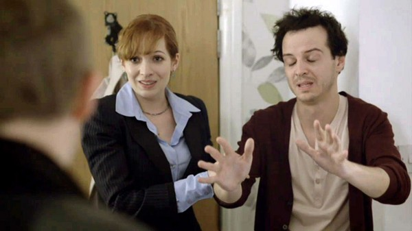 Katharine Parkinson as Kitty Riley in the BBC series Sherlock looking at Sherlock Holmes with hand on arm of Andrew Scott as James Moriarty who has day old stubble on face and looks disheveled.