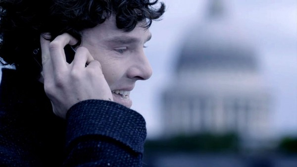 Benedict Cumberbatch as BBC Sherlock Holmes smiling on the roof of Bart's talking on a mobile phone