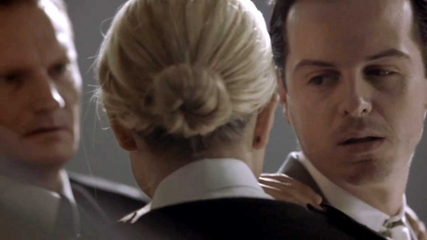 Andrew Scott as James Moriarty in the BBC series Sherlock looks seductively at a policewoman with her hair in a tight bun