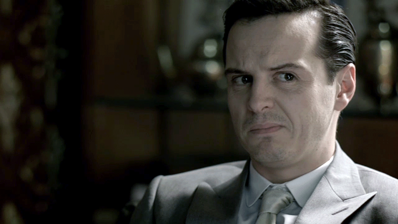 Andrew Scott as James Moriarty in BBC Sherlock in grey suit looking skeptical