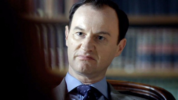 Mark Gatiss as Mycroft Holmes in BBC Sherlock with a sour look upon his face