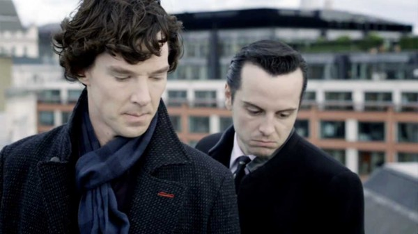 Benedict Cumberbatch as Sherlock Holmes and Andrew Scott as James Moriarty peer down over a building ledge.
